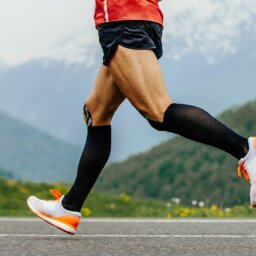 legs men runner in black compression socks run in background of mountains